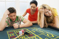 Couple losing bet with friend at roulette table young large mixed race female Royalty Free Stock Images