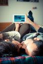 Couple in love on the bed using tablet at home Royalty Free Stock Photography