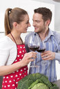 Couple in love cooking together in the kitchen - drinking red wi Royalty Free Stock Photo