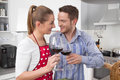 Couple in love cooking together in the kitchen and have fun re celebrate drinking red wine Royalty Free Stock Photography