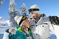 Couple in love holding eachother on the ski slopes cheerful of skiers looking at each other s eyes Royalty Free Stock Photo