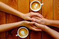 Couple in love holding hands in a cafe top view on wooden table Royalty Free Stock Image