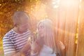 Couple in love hugging happy young and kissing outside next to the wooden fence Stock Images