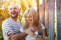 Couple in love hugging happy young and kissing outside next to the wooden fence Stock Photos