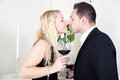 Couple in love kissing attractive elegant young while holding large glasses of red wine their hands as they celebrate their Royalty Free Stock Image