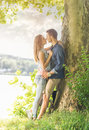 Couple in love on the lake beneath the trees kissing Stock Photos