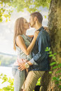 Couple in love on the lake beneath the trees kissing Royalty Free Stock Photography