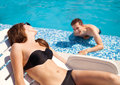 Couple in love near swimming pool young beautiful women sunbathing the and flirting with a young guy Stock Images