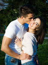 Couple in love in a park happy hugging and smiling kissing on the cheek Stock Image