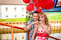 Couple in love with red balloons young happy on the bridge Royalty Free Stock Photo