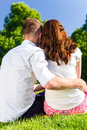 Couple in love sitting on park lawn enjoying sun hugging Stock Photos