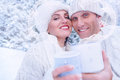 Couple in love in snow forest with heart frame from steam