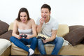 Couple in love on sofa sitting and playing video games in living