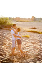 Couple in love walks on the banks of the river denim shorts and a white shirts Royalty Free Stock Images