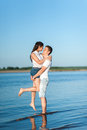 Couple in love walks on the banks of the river denim shorts and a white shirts Royalty Free Stock Photo