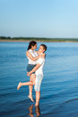 Couple in love walks on the banks of the river denim shorts and a white shirts Royalty Free Stock Photos