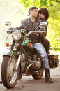 Couple of lovers sitting by motorcycle Royalty Free Stock Photos