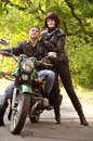Couple of lovers sitting by motorcycle Stock Photography