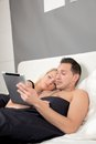Couple lying in bed reading a tablet pc close together cuddling with copyspace Royalty Free Stock Image