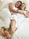 Couple lying in bed smiling Royalty Free Stock Image