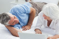 Couple lying in bed and using a laptop mature Stock Image