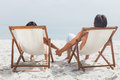 Couple lying on deck chairs holding their hands beach Royalty Free Stock Photography