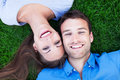 Couple lying on grass with their face close together Stock Image