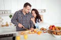 Couple making fresh organic juice in kitchen together. A young man slices a baguette. A woman standing near her