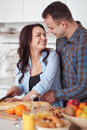 Couple making fresh organic juice in kitchen together. A young woman in a blue shirt slices a baguette. A man is hugging