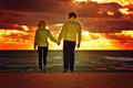 Couple man and woman in love walking on beach seaside holding hand in hand with beautiful sunset sky scenery people romantic Stock Photo