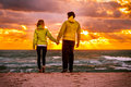 Couple man and woman in love walking on beach seaside holding hand in hand with beautiful sunset sky scenery people romantic Royalty Free Stock Image