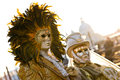 Couple of masked people posing during traditional venice carnival in gold Stock Photography