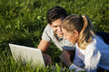 Couple on meadow using wi-fi for Internet Stock Images