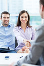 Couple meeting with financial adviser shaking hands to real estate agent at home Stock Photography