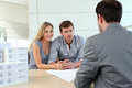 Couple meeting real estate agent in agency talking to construction planner Stock Photography