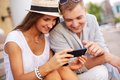 Couple with mobile phone happy girl and her boyfriend using outside Stock Image