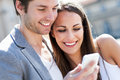 Couple with mobile phone smiling Royalty Free Stock Images