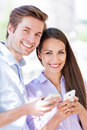 Couple with mobile phones smiling Stock Image