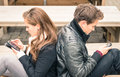 Couple in a moment of mutual disinterest distracted by smartphones Royalty Free Stock Photo