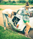 Couple in a moment of troubles during a vintage classic car trip Royalty Free Stock Photo