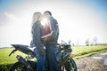 Couple and motorbike of lovers kissing with in the background two bikers stop in the countryside Royalty Free Stock Photo