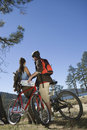 Couple with mountain bikes in recreation area rear view of a young standing Stock Photos