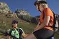 Couple mountain biking in valley, sitting on bicycles, taking break, low angle view Royalty Free Stock Photo