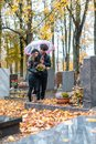 Couple mourning a deceased loved one on cemetery in fall Royalty Free Stock Photo