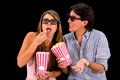 Couple at the movies wearing d glasses isolated over black background Stock Photos