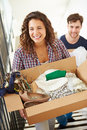 Couple moving into new home carrying box upstairs happy with clothes and shoes Royalty Free Stock Image