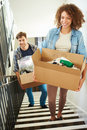 Couple moving into new home carrying box upstairs with items in smiling Stock Image