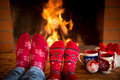 Couple near fireplace relaxing at home feet in christmas socks winter holiday concept Stock Photos
