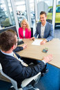 Couple negotiating sale contact for car buying at dealership and price with salesman Stock Photos