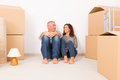Couple at new home happy mature sitting on the floor in their boxes lamp and carpet in background Royalty Free Stock Images